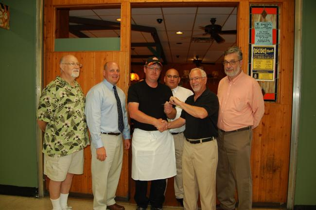 CHRIS PARKER/TIMES NEWS Lansford Alive! officer Bob Silver, fifth from left, presents the organization's first grant check to Bowie's Family Restaurant owner Robert Middleton. Looking on are, from left: Lansford Alive! member Martin Ditsky; state…