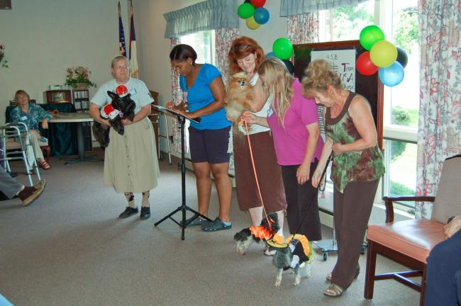 LINDA KOEHLER/TIMES NEWS Second from left, Ashley Bowden, activity assistant, announces some of the winners at Mrs. Bush's Personal Care Homes 6th Annual Pet Show. They were, left to right: Mary Jane Sterling with King Dougal; Ashley; Christel…