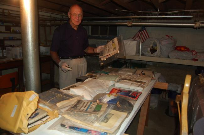 TERRY AHNER/TIMES NEWS Peter Kern, a member of the Palmerton Area Heritage Center, rummages through the memorabilia that had been inside the Time Capsule that was buried in the Palmerton Borough Park nearly 25 years ago. Here, Kern is shown holding…