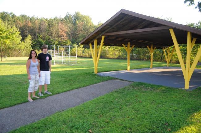 RON GOWER/TIMES NEWS Monica Marshall, left, president of the Summit Hill Recreation Commission, and Eagle Boy Scout Tyler Devonshire of Summit Hill, discuss improvements made to the pavilion at the Ginder Field Park. The roof was replaced and the…