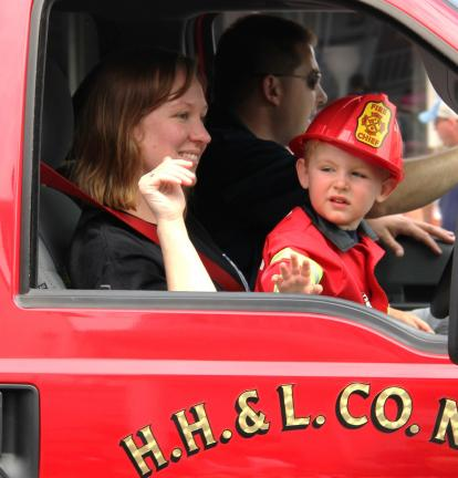 ANDREW LEIBENGUTH/TIMES NEWS Dru Herber, 2, sits on his mother's, Leigh's, lap while his father, Captain J.T., drives a Pine Grove H. H. & L. fire truck.