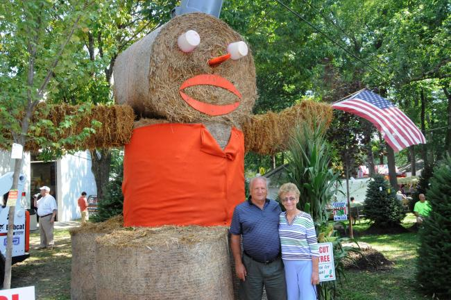 "RON GOWER/TIMES NEWS Clarence ""Topsy"" Derby and his wife, Nancy, are dwarfed by a huge scarecrow displayed by Old Homestead Tree Farm at the West End Fair in Gilbert."