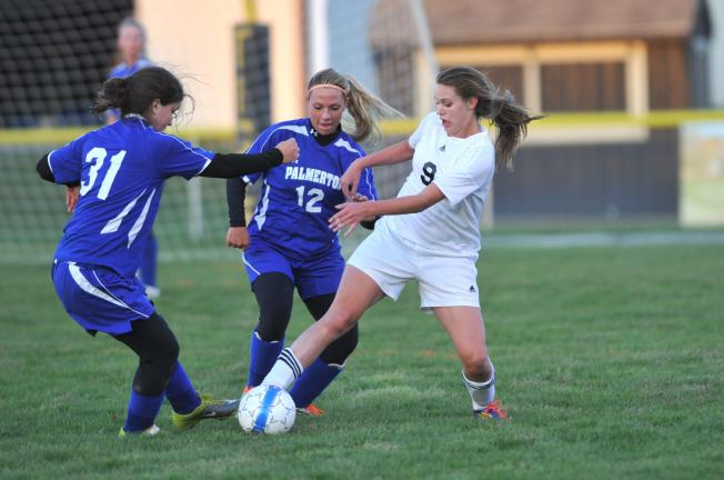 TIMES NEWS FILE PHOTO Northwestern's Sarah Segan (right) battles with Palmerton players Sabreena Strauch (31) and Shana Ahner (12) for possession in a game last spring. For the first time, the PIAA has moved girls soccer to be played as a fall sport…