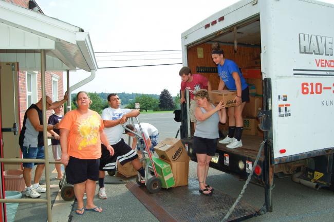 LINDA KOEHLER/TIMES NEWS Two Pleasant Valley High School seniors, Hunter Deihl, fourth from left, and Hailey Marini, right, and members of their family unload boxes of clothing they collected for a free clothing give away.