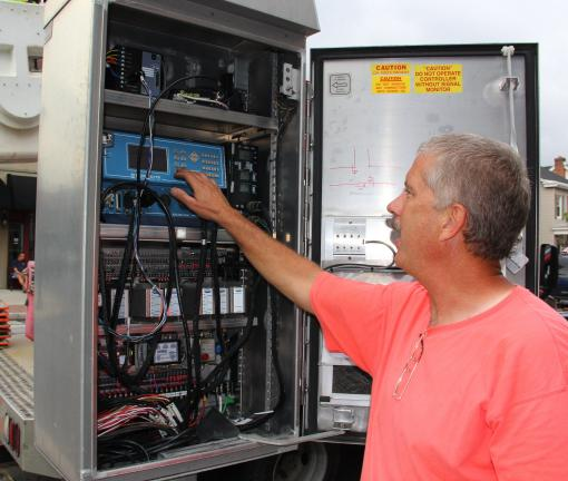 Electrical contractor Walt Weniger of Bruce & Merrilees updates the timing at a control box at the East Broad and Pine Street intersection.