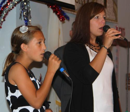ANDREW LEIBENGUTH/TIMES NEWS Michaela, 13, and her mother Rosemarie Noftz sing patriotic songs during Tamaqua's 9/11 memorial service.