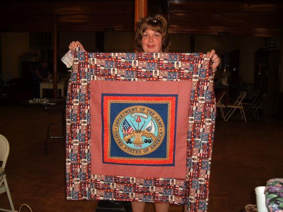 Dave Wargo/special to the times news Carbon County Quilters Guild Treasurer Ellen Meli displays a custom quilt top of her own design that will eventually be backed and sewed to be sent to wounded troops through Andrews Air Force Base as part of the…