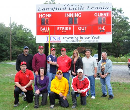 Ron Gower/TIMES NEWS Taking part in the dedication of a new scoreboard at the Lansford Little League Field this week are, front l-r, Glen Karnish, vice president of the Lansford Little League; Jennifer Karnish, financial accountant at Jim Thorpe…