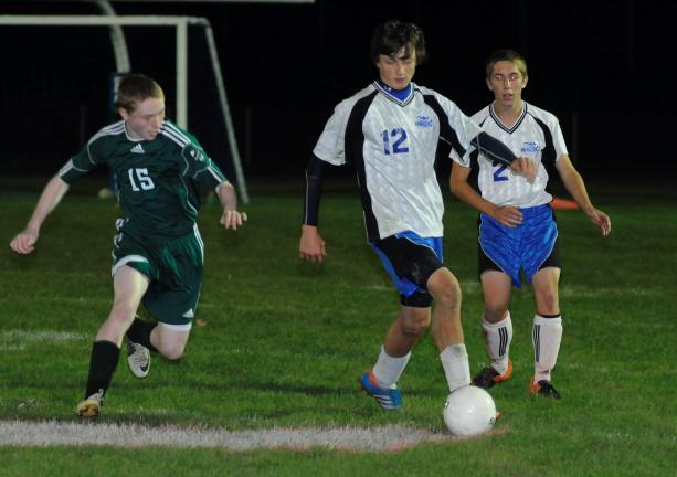 Palmerton's Jonathan Schwarz (12) dribbles the ball away from Pen Argyl's Tyler Avery (15). The Bombers' Ty Green (2) moves in from behind.