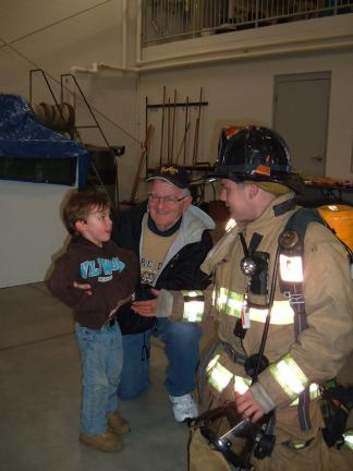 DAVID WARGO/SPECIAL TO THE TIMES NEWS Summit Hill resident Stanley Szczecina (center) and great grandson Lucas Sloboda who is 3 years old (left) meet Summit Hill firefighter Brandon Miller who is demonstrating turn out gear so that little children…