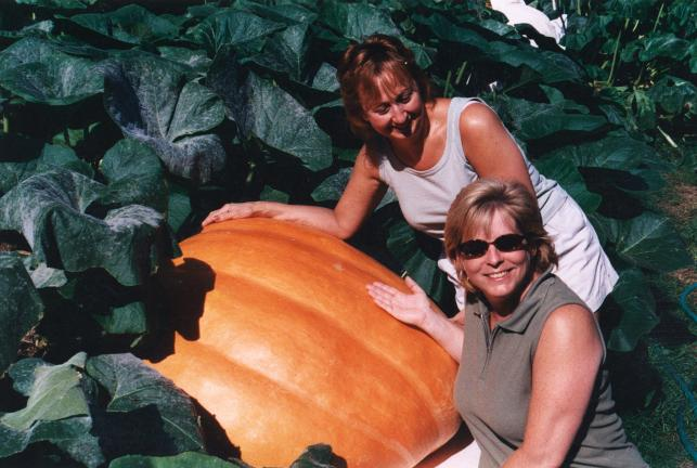 Goddaughter Brenda and wife Diane pose with a giant pumpkin in the garden.