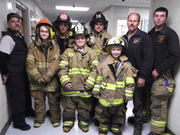Carol Zickler/special to the times news Blake Morgans, fifth grade; and Robbie Stempa, fourth grade, standing in front, both students from Panther Valley Elementary School get a chance to try on gear of the firefighters. Firefighters around the boys…