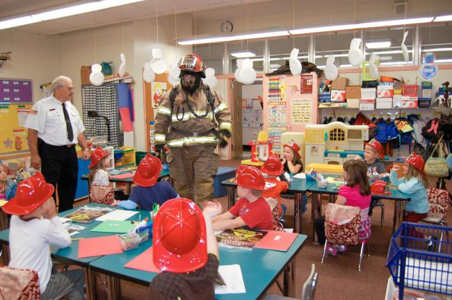 Gail Maholick/TIMES NEWS Bruce Wolfe, Franklin Township fire chief introduces firefighter Shawn Sheckler, who is in full firefighting gear, to kindergarten children at Franklin Elementary School.