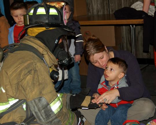 CHRIS PARKER/TIMES NEWS PathStone HeadStart teacher Angela Krapf, holding Nathan Rolon, encourages him to shake hands with firefighter Jonathan Oakes, who looks a little scary in full gear.