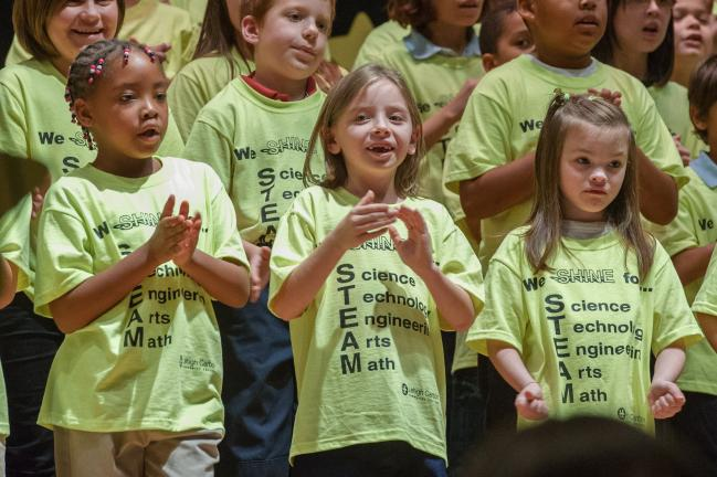 AMY MILLER/TIMES NEWS L.B. Morris Elementary SHINE students, Crystal Edwards, left; Kacie Weaver, center; and Arwen McFarland sing with their classmates during the opening act of the 13th Annual Lights On Afterschool Program, held at Panther Valley…