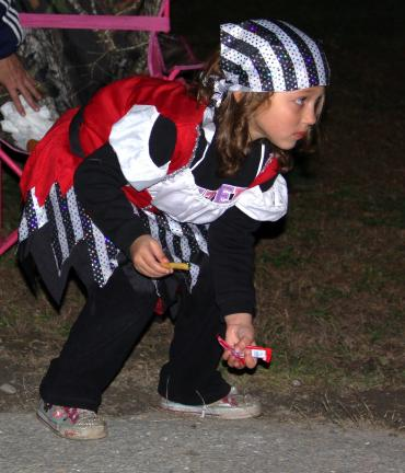 Addison Krall, 5, dressed as a pirate, leans down for candy thrown from a passing firetruck.