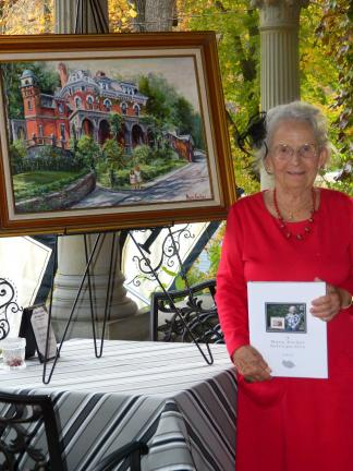 Mary Kocher, holding her book, stands near a painting commissioned by Cindy Gasper, which depicts the Harry Packer Mansion and Gasper's two eldest daughters in the foreground.