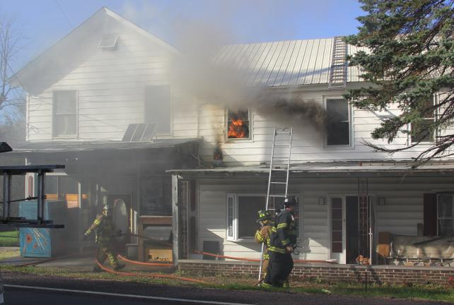 ANDREW LEIBENGUTH/TIMES NEWS Emergency personnel responded to 562 Pine Creek Drive (SR54) around 3:15 p.m. yesterday after a passer-by reported seeing people on the roof with buckets and a garden hose trying to extinguish a fire.