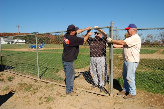 Gail Maholick/TIMES NEWS Larry Strohl, Bill Hill and Wayne Wentz, are replacing the fencing around the Babe Ruth Field at the Christman Field in Franklin Township. Hill and Wentz are also Lehighton Area School board directors.