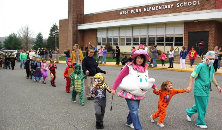 ANDREW LEIBENGUTH/TIMES NEWS Parents and family members watched as costumed students and staff paraded around the parking lot of the West Penn Elementary School during the school's annual Halloween parade held on Friday. Kindergarteners Damien…