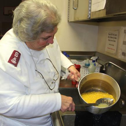 ANDREW LEIBENGUTH/TIMES NEWS Major Margaret Johnson prepares corn for visitors. The main course consisted of ham, buttered noodles,corn, garlic bread, ice cream, drinks and so on.