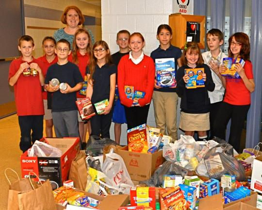 VICTOR IZZO/SPECIAL TO THE TIMES NEWS Standing with just part of the food donations that the student body collected are L.B. Morris Elementary School 4th, 5th, and 6th grade students of the month, left to right: Darien Fegley; Ylana Nieves; Jack…