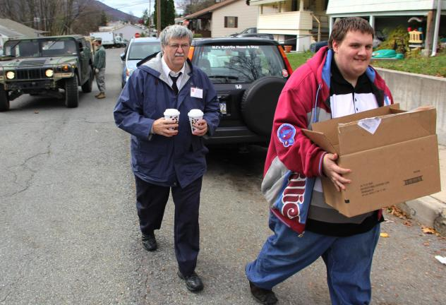 ANDREW LEIBENGUTH/TIMES NEWS Tamaqua Salvation Army volunteers Jesse Durning and son, Frank Latham, carry hot coffee and meals to homes still without power in Palmerton. Volunteers made three trips to Palmerton over the weekend.