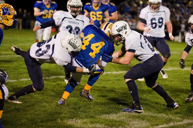 bob ford/times news Tamaqua's Nick Hollenbach (left) and Tyler Hope (right) combine to bring down Marian's Dylan Quirk. (44).
