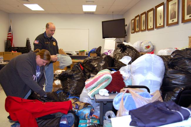 CHRIS PARKER/TIMES NEWS Kira Michalik, foreground, and fiance Kevin Steber sort and fold donated clothing in Diligence Fire Co., Summit Hill.