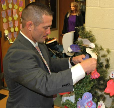Tamaqua Elementary Schools Principal James Fasnacht places a paper butterfly made by students on one of six veteran butterfly trees.
