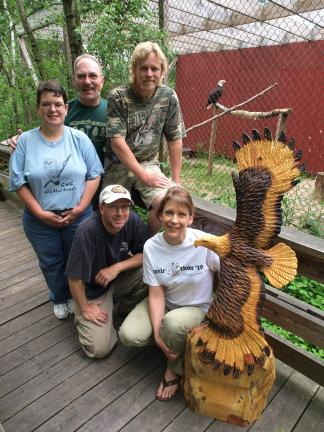 AL ZAGOFSKY/FILE PHOTO A chainsaw art sculpture of a bald eagle in flight is a monument to a falconry volunteer who helped create the Carbon County Environmental Education Center's Birds of Prey program. Pictured are left to right, rear, Jeannie…