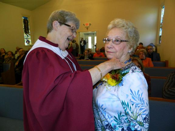 JUDY DOLGOS-KRAMER/SPECIAL TO THE TIMES NEWS Clara Moyer pins a corsage on Anna Moser at St. Paul's Lutheran Church in Albrightsville Sunday. Moser was honored for her nearly 60 years of service to the church.