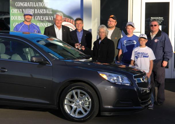 ANDREW LEIBENGUTH/TIMES NEWS Pictured with a new 2013 Chevy Malibu are, from left, are Cy Rother, Vice President, Tamaqua Area Baseball Association; Jim Corazza, owner, Fairway Chevrolet; Richie Molinaro, Director of Marketing and Advertising;…