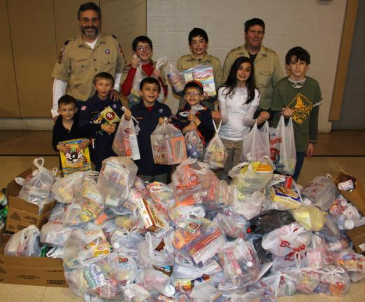 ANDREW LEIBENGUTH/TIMES NEWS Pictured a portion of the 1,400 pound donation of food, from front left, are scouts Michael Lewis, 5; Adam Bachert, 7; Derek DeAngelo, 8; Eric Richardson, 7; volunteer Ashley DeAngelo, 12; and Aidan Bonner, 11. From back…