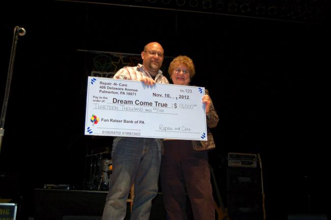 Gail Maholick/TIMES NEWS Wayne Halliday, coordinator of the annual Tech-Net Comedy Night held Saturday at Penn's Peak, presents a check of $13,000 to Eileen Thompson, president of Dream Come True, Blue Ridge Chapter.