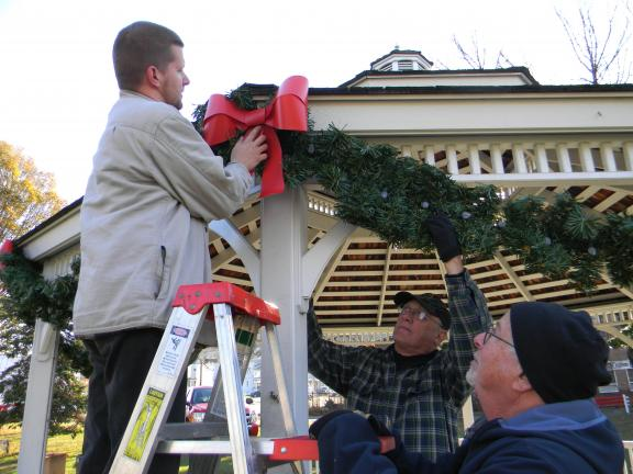 LISA PRICE/SPECIAL TO THE TIMES NEWS Lansford Alive President Chris Ondrus, Bob Dobosh and vice-president Bob Silver decorate the borough in advance of the Christmas tree-lighting ceremony this weekend.