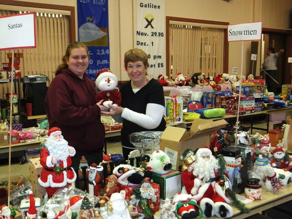 "STACEY SOLT/SPECIAL TO THE TIMES NEWS Amanda Tertel, left, and Sarah Dalton, volunteers at the Trinity Thrift Store in Lehighton, help to set up the ""snowman"" display at the annual Christmas sale. The Trinity Thrift Store's Christmas sale will…"