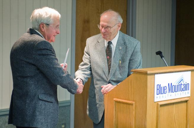 BOB FORD/TIMES NEWS Henry Bisbing, president of the BMHS auxiliary, shakes hands with Carl Merluzzi during Merluzzi's retirement celebration at the hospital Tuesday afternoon.