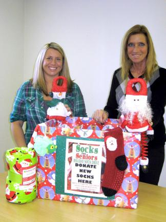 "STACEY SOLT/SPECIAL TO THE TIMES NEWS Jessica Kutza, left, and Mary Ann Dulaney show a ""Socks for Seniors"" drop-off box. The mother-daughter team is organizing a gift drive for local senior citizens through the national ""Socks for Seniors"" program,…"