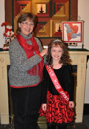 DONALD R. SERFASS/TIMES NEWS Callista Fannock, third grade student at Tamaqua Elementary School, will reign as the 2012 Little Miss Spirit of Christmas. Presenting the tiara Wednesday is Judy Hoppes, contest chairperson.