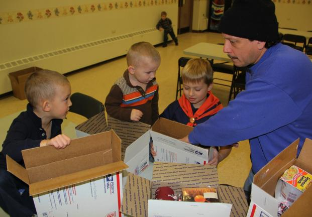 ANDREW LEIBENGUTH/TIMES NEWS Scouts, parents and volunteers spent time recently packing boxes and boxes of care package items they collected to send to the Hometown unit and other local military personnel serving abroad. The care packages are filled…