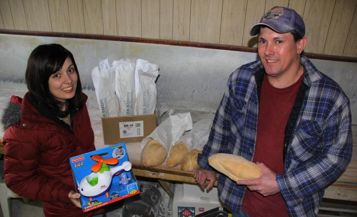 ANDREW LEIBENGUTH/TIMES NEWS Amber Berger-Murphy and Larry Padora hold freshly made bread. Anyone can drop off a new toy in exchange for a fresh loaf of bread.
