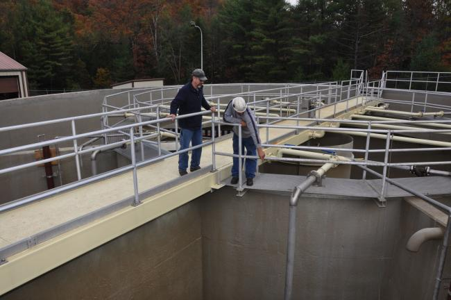 AMY MILLER/TIMES NEWS Bob Pilla, Nesquehoning Wastewater Treatment Plant operator, left; listens as John Ortlieb, foreman for Eastern Environmental of Green Lane, Pa., points out what the company did during the rehabilitation of the wastewater…
