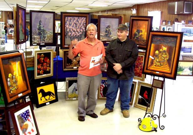 SPECIAL TO THE TIMES NEWS Right, Griz Gannon, president of the Jackson Township Volunteer Fire Co., accepts donations from the first annual Monroe-Carbon County Autumn Art Show from artist Andy Collazo, who also donated the painting on the right, …