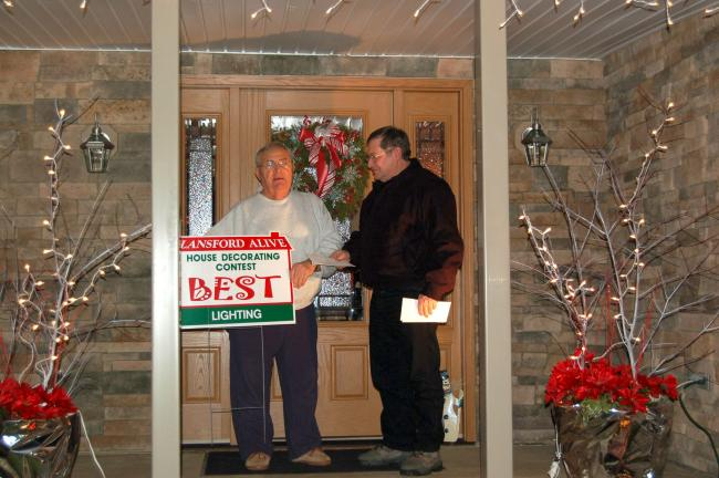 "CHRIS PARKER/TIMES NEWS Lansford Alive 11th Annual Christmas House Decorating Contest judging committee member Tony Walck presents one of two awards in the ""Lighting"" category to former Lansford mayor George Krajnak. Krajnak's daughter, Janelle…"
