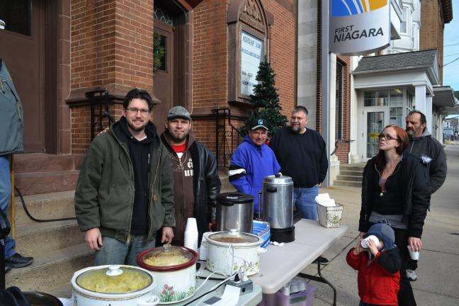 SHERI RYAN/SPECIAL TO THE TIMES NEWS ABOVE: The Rev. Jeremy Benack, left, and members of Grace Community Church shared hot chili, soup and cocoa with people at the second annual cash giveaway as part of Lansford Days of Christmas. With Benack are,…