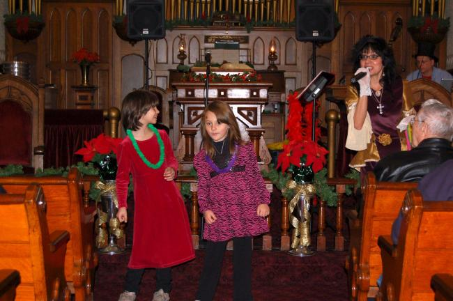 CHRIS PARKER/TIMES NEWS Cherokee Levan, 7, and Chelsea Kurtz, 6, sway to the music as Leilani Chesonis, right, sings Mele Kalikimaka at the Victorian Christmas program at the Lansford Historical Society on Sunday.