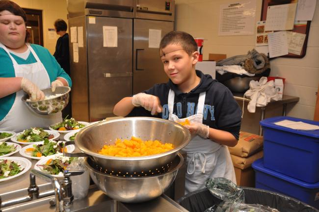 "AMY MILLER/TIMES NEWS SHINE Career Academy student Devin Ebert helps to prepare the salads for the students' parents during the finale of the ""Molecular Gastronomy"" session of the Carbon County SHINE Career Academy."