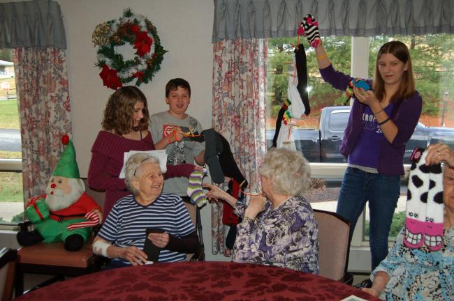 LINDA KOEHLER/TIMES NEWS Palmerton Area Junior High students collected socks to be given to senior citizens. They visited Mrs. Bush's Personal Care Home in Kunkletown, where they gave a pair of socks to each resident. Here Adrianna Romanishan,…