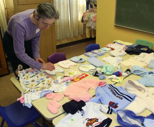 "ANDREW LEIBENGUTH/TIMES NEWS Volunteer Bonnie Smith looks over items ""for sale"" in their ""Baby Bucks"" store. These items are awarded at no charge to families."